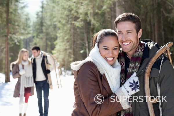 Stock Photo: 1775R-30161 Portrait of smiling couple with sled in snowy woods