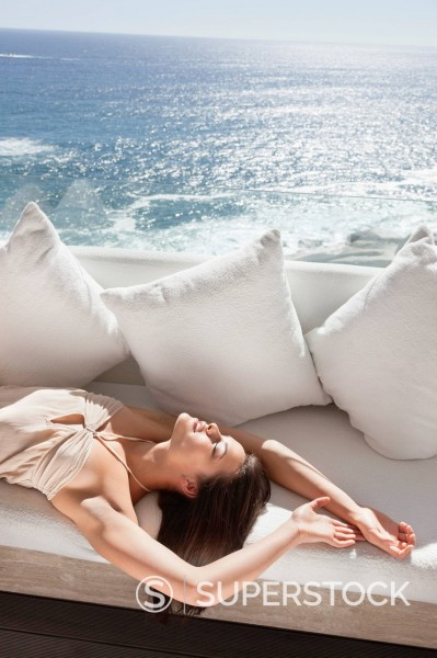 Stock Photo: 1775R-30166 Serene woman laying on sofa overlooking ocean