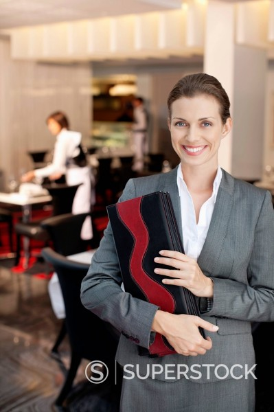 Portrait of smiling hostess in restaurant : Stock Photo