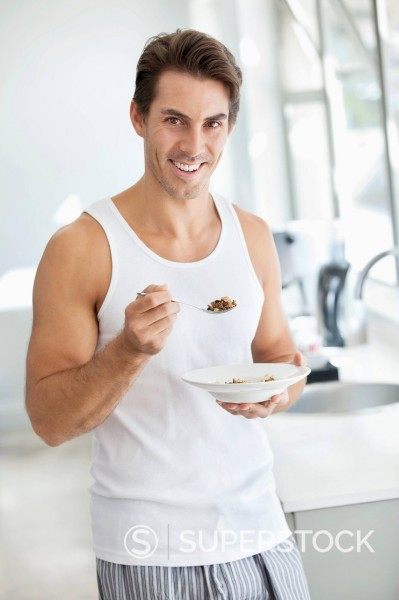 Portrait of smiling man eating cereal in kitchen : Stock Photo