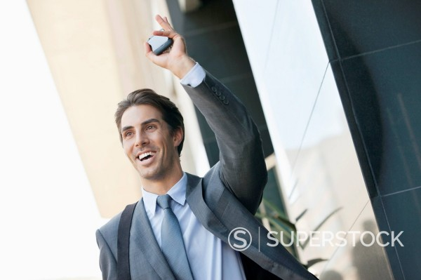 Stock Photo: 1775R-30192 Smiling businessman holding cell phone and waving