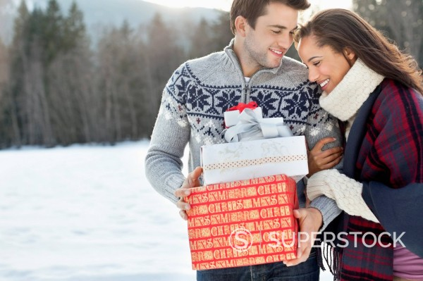 Stock Photo: 1775R-30215 Smiling couple hugging and holding Christmas gifts in snow