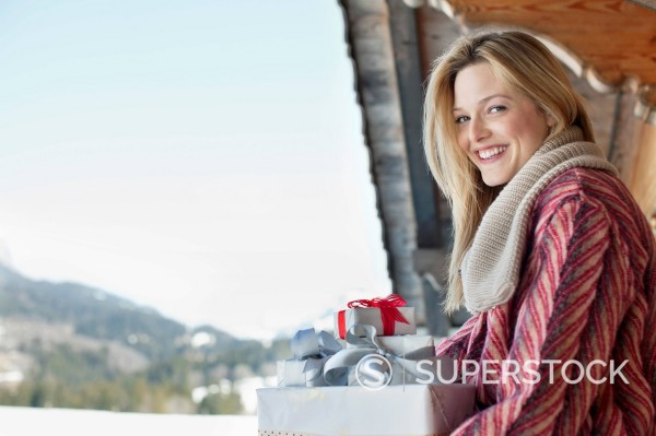 Portrait of smiling woman with Christmas gifts : Stock Photo