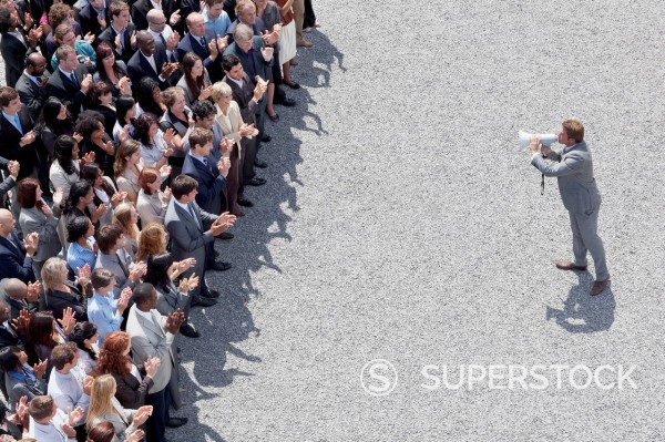 Businessman with bullhorn speaking to crowd : Stock Photo
