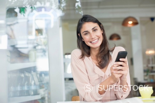 Stock Photo: 1775R-30268 Portrait of smiling woman holding cell phone in café window