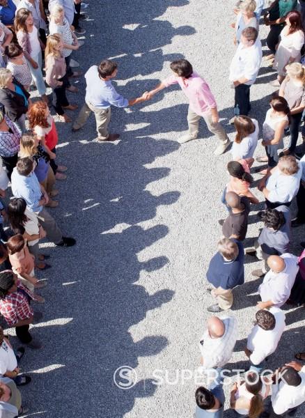 Men handshaking between separate groups : Stock Photo