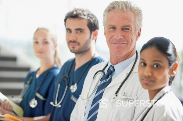 Portrait of smiling doctors and nurses in a row : Stock Photo