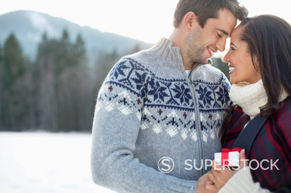 Smiling couple face to face in snowy field : Stock Photo