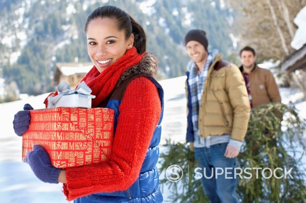Stock Photo: 1775R-30304 Portrait of friends with fresh cut Christmas tree and gifts in snow