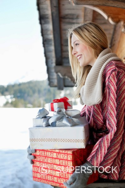 Smiling woman holding Christmas gifts on cabin porch : Stock Photo