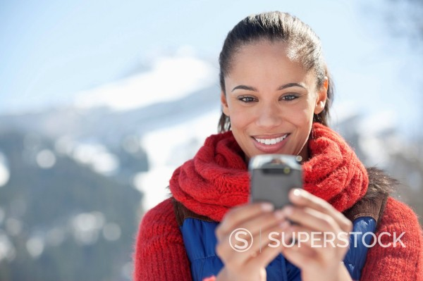 Smiling woman checking cell phone : Stock Photo
