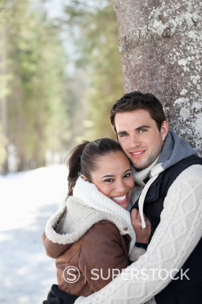Stock Photo: 1775R-30309 Portrait of smiling couple leaning against tree trunk in snowy woods