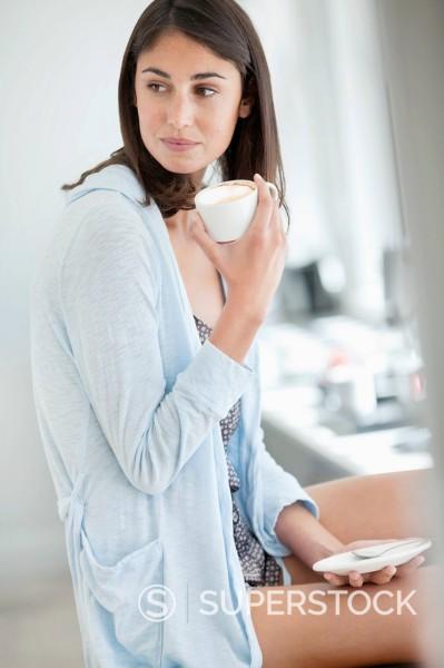 Stock Photo: 1775R-30335 Woman drinking coffee in pajamas