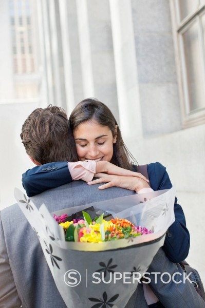 Woman hugging man with flowers behind back : Stock Photo