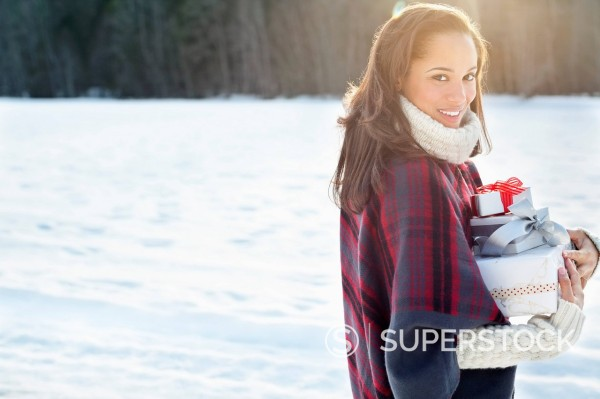 Stock Photo: 1775R-30339 Portrait of smiling woman carrying Christmas gifts in snow
