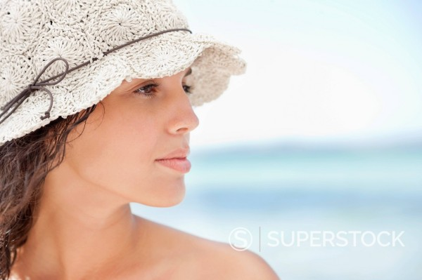 Stock Photo: 1775R-30346 Close up of serious woman in sun hat on beach