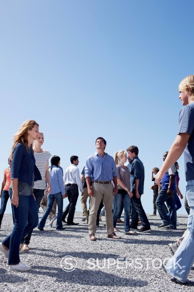 Man standing and looking up among crowd of walking people : Stock Photo
