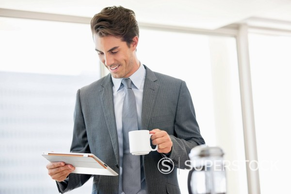 Stock Photo: 1775R-30356 Businessman drinking coffee and looking down at digital tablet