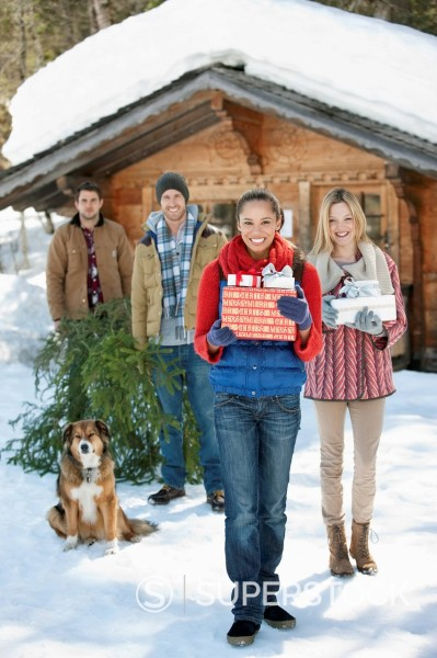 Stock Photo: 1775R-30366 Portrait of smiling couples and dog with fresh cut Christmas tree and gifts in front of cabin