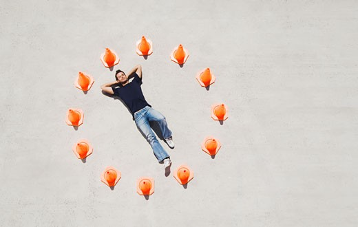 Man lying down in circle of traffic cones with arms up : Stock Photo
