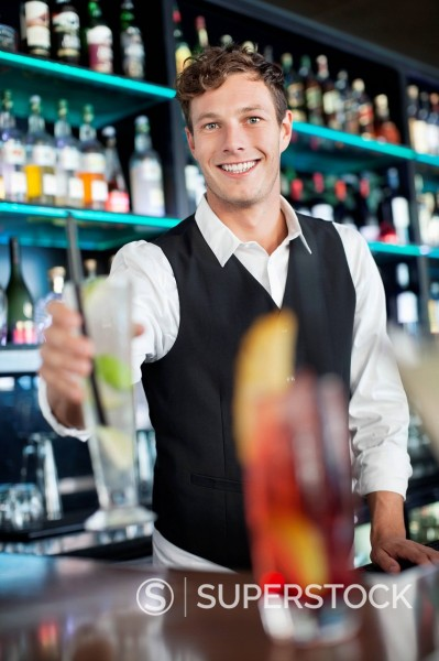 Stock Photo: 1775R-30405 Portrait of smiling bartender holding cocktail