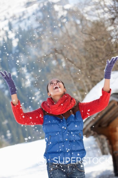 Stock Photo: 1775R-30409 Happy woman throwing snow and looking up