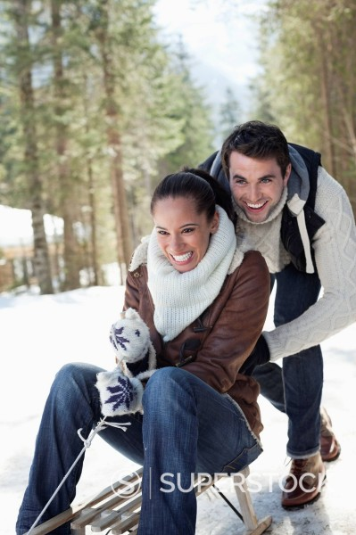 Stock Photo: 1775R-30412 Smiling couple sledding in snowy woods