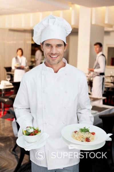 Stock Photo: 1775R-30427 Portrait of smiling chef holding salad and entree
