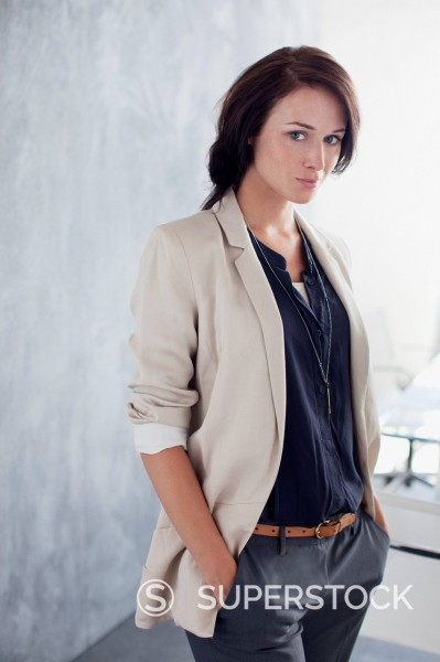 Stock Photo: 1775R-30432 Portrait of confident businesswoman with hands in pockets in office