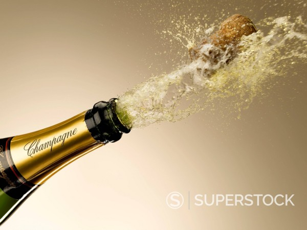 Champagne and cork exploding from bottle : Stock Photo
