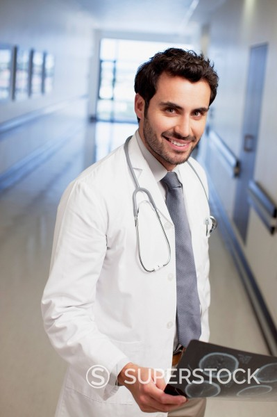 Stock Photo: 1775R-30475 Portrait of smiling doctor holding x_ray in hospital corridor
