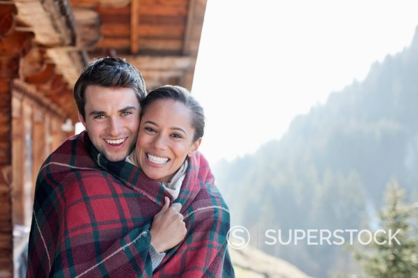 Portrait of smiling couple wrapped in a blanket on cabin porch : Stock Photo
