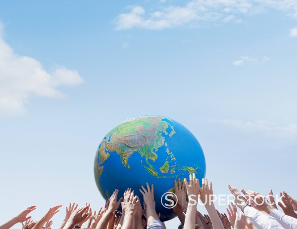 Crowd reaching for globe : Stock Photo
