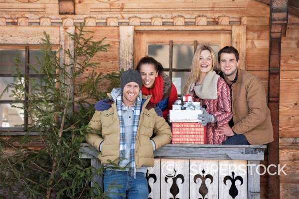 Stock Photo: 1775R-30516 Portrait of smiling couples with fresh cut Christmas tree and gifts in front of cabin