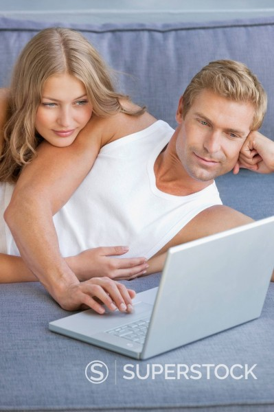 Stock Photo: 1775R-30533 Couple laying on sofa and using laptop