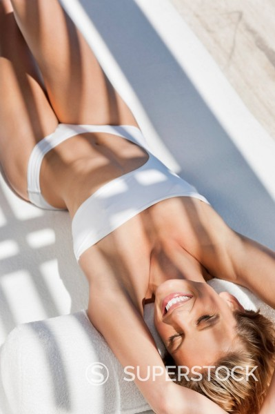 Stock Photo: 1775R-30535 Smiling woman in bathing suit laying on lounge chair