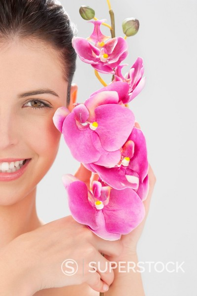 Close up portrait of smiling woman holding pink orchid : Stock Photo