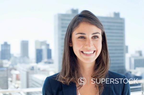 Smiling businesswoman on urban balcony : Stock Photo