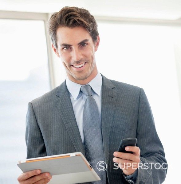 Stock Photo: 1775R-30578 Portrait of smiling businessman holding cell phone and digital tablet
