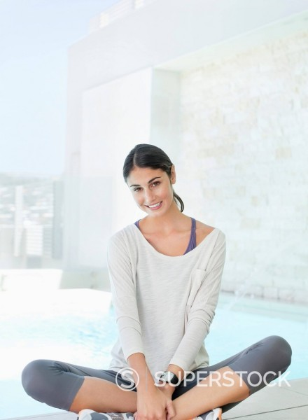 Stock Photo: 1775R-30580 Portrait of smiling businesswoman sitting cross_legged at poolside