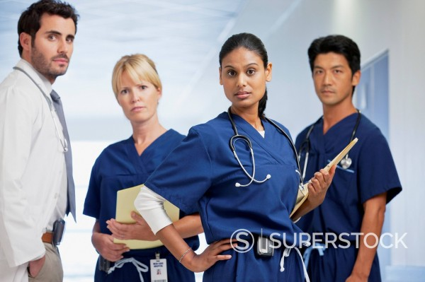Portrait of serious doctor and nurses in hospital corridor : Stock Photo