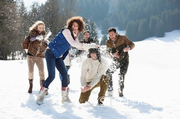 Friends throwing snowballs in field : Stock Photo