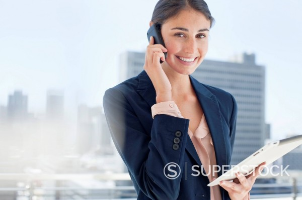 Portrait of smiling woman holding digital tablet and talking on cell phone : Stock Photo
