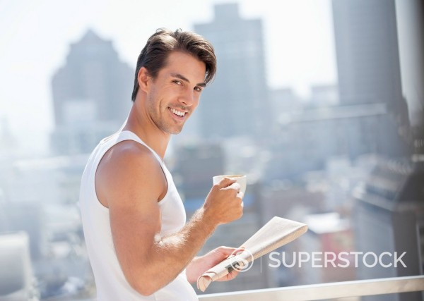 Stock Photo: 1775R-30613 Portrait of smiling man drinking coffee and reading newspaper on urban balcony