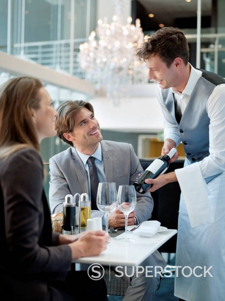 Sommelier presenting wine bottle to couple in restaurant : Stock Photo