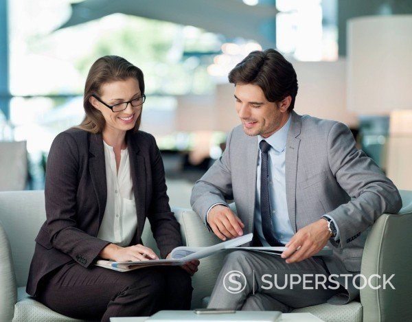 Businessman and businesswoman working in lobby : Stock Photo