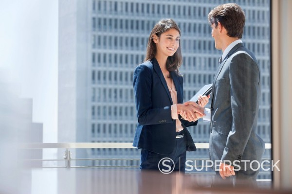 Stock Photo: 1775R-30621 Smiling businessman and businesswoman shaking hands on urban balcony