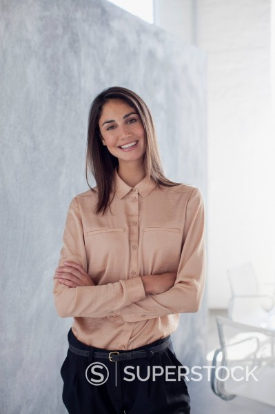 Stock Photo: 1775R-30655 Portrait of smiling businesswoman with arms crossed in office