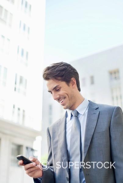 Smiling businessman checking cell phone : Stock Photo