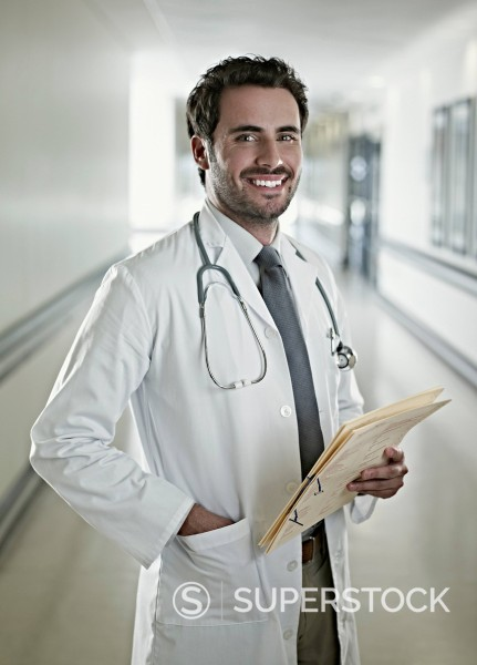 Stock Photo: 1775R-30681 Portrait of confident doctor holding medical record in hospital corridor
